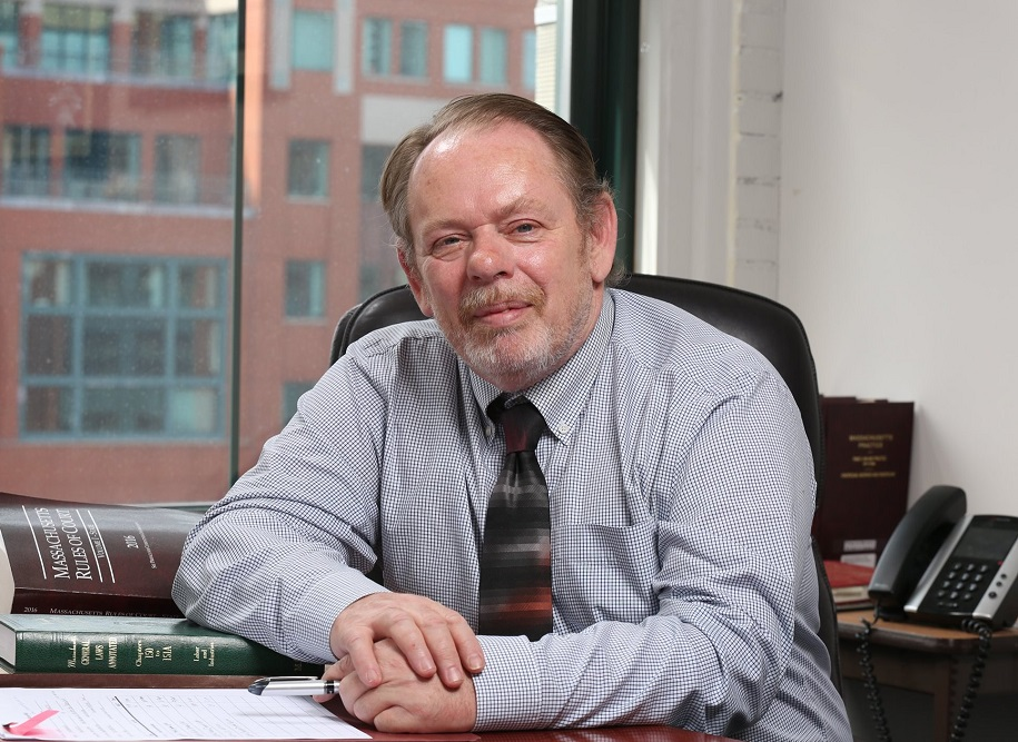 Photo of Brian Flynn sitting in a GBLS office with files and law books on the table in front of him. Brian is wearing a button down shirt and a tie.