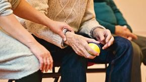 Close up picture of a young woman's hand resting on an elderly man's arm as the man holds a tennis ball.