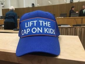 "Blue baseball cap with the phrase ""Lift the Cap on Kids"" emblazoned on the front."