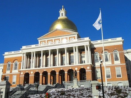Sunlight photo of the Massachusetts State House with the sunlight gleaming off of its golden dome.