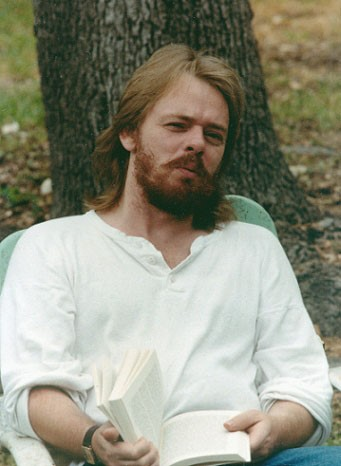 A picture of Brian Flynn in his 20s. Brian has long hair and a beard, he is wearing a white shirt and is sitting down outdoors holding a book.
