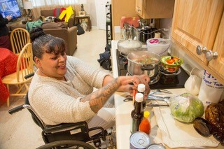 Woman in wheelchair is able to cook in her new accessible apartment