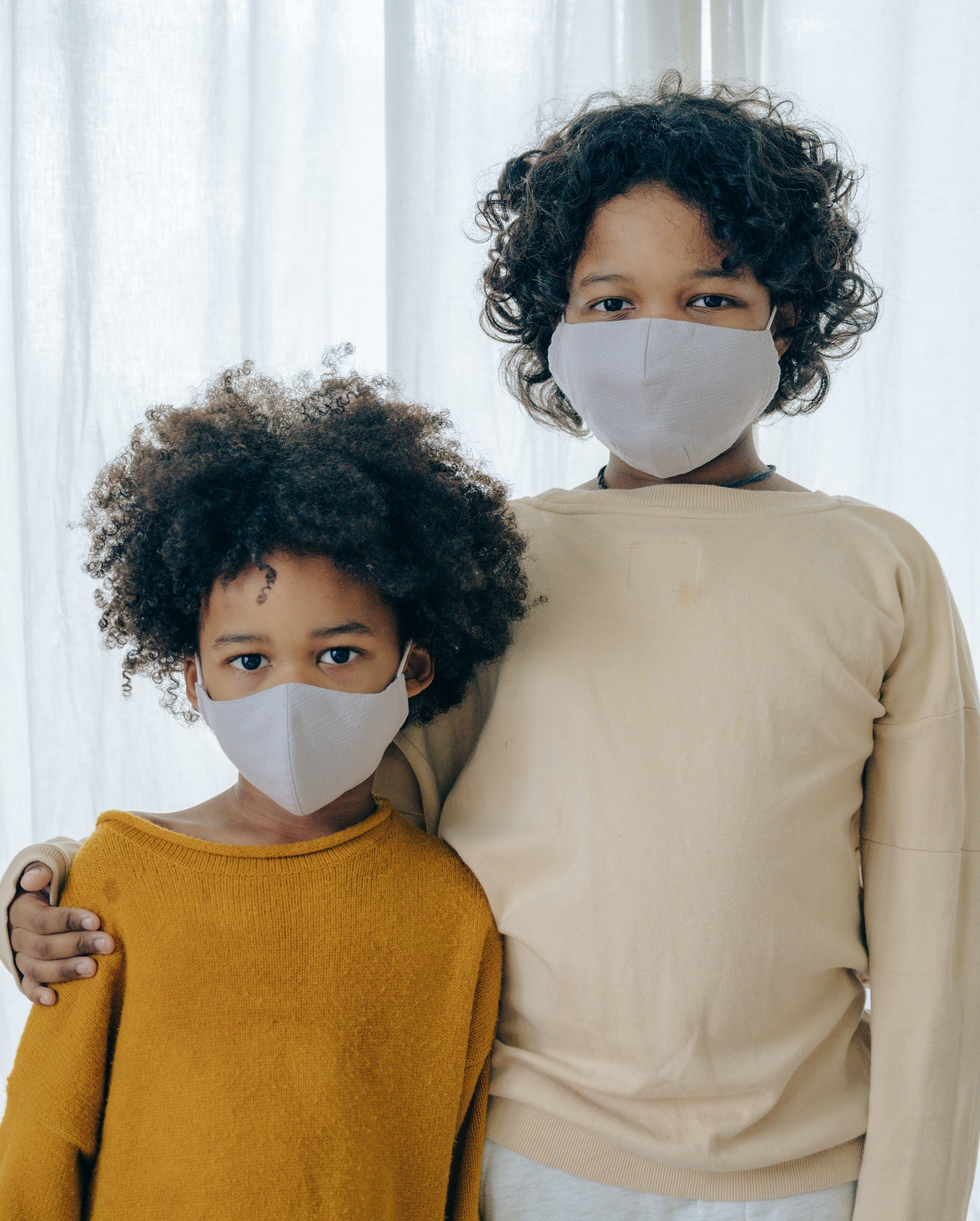 Photo of two siblings standing side by side, dressed in pastel colors and wearing face masks.