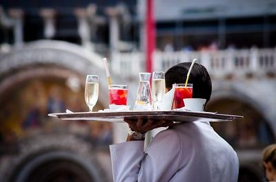 A waiter carries a tray of drinks.